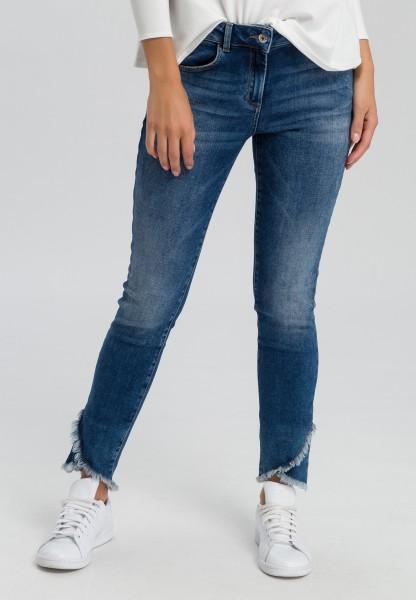 Jeans with curved fringed hem